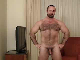 bearded homosexual bear disrobes in his living